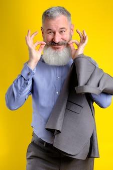 Retrato de estúdio barbudo homem engraçado terno cinza, olhando para a câmera, estilo de vida de profissão de trabalho, fundo amarelo.