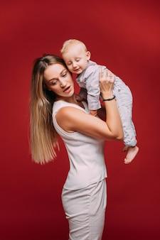 Retrato de estúdio da bela mãe caucasiana, segurando o filho dela com cabelo loiro nos braços na parede vermelha.