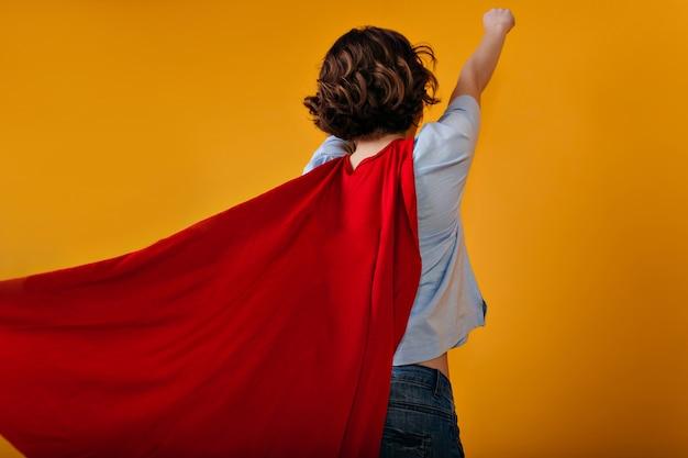 Retrato de estúdio das costas de uma garota despreocupada brincando com uma fantasia de super-herói