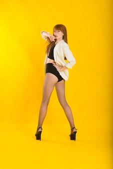 Retrato de estúdio de corpo inteiro de uma mulher bonita em uma jaqueta xadrez, meia-calça de bolinhas brancas e botas