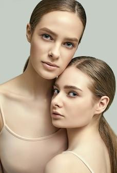 Retrato de estúdio de duas lindas garotas sensuais com a pele clara do rosto jovem