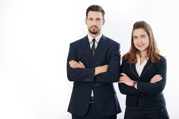 Retrato de estúdio de empresário confiante sorridente e empresária em pé com os braços cruzados