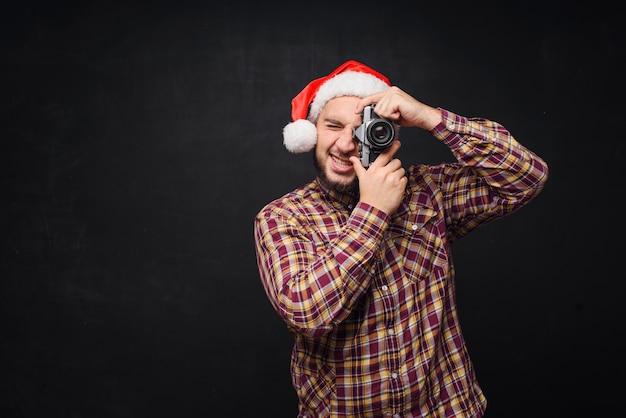 Retrato de estúdio de engraçado e surpreso barbudo homem usando chapéu de papai noel, segurando uma câmera retro, fazendo uma foto. espaço para texto. preto