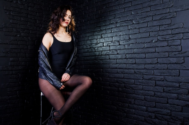 Retrato de estúdio de garota morena sexy no casaco de cabedal preto contra a parede de tijolos.