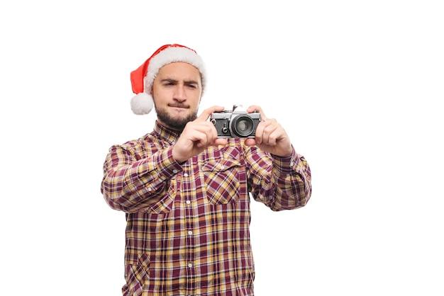 Retrato de estúdio de homem barbudo com chapéu de papai noel segurando uma câmera retro, fazendo uma foto. fundo branco isolado