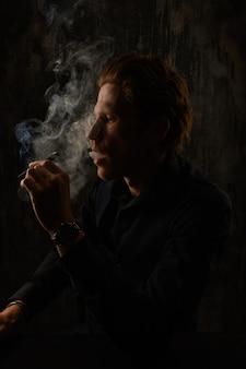 Retrato de estúdio de homem e cigarro fumando contra um fundo escuro