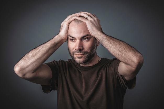 Retrato de estúdio de homem pensativo com as mãos segurando a cabeça dele.