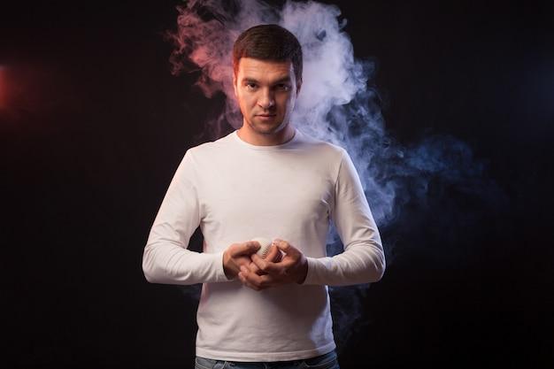 Retrato de estúdio de jogador desportista muscular posando em fundo preto em fumaça colorida com uma bola de beisebol na mão.
