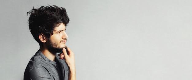 Retrato de estúdio de jovem barbudo pensativo olhando para longe, no fundo texturizado vazio de cinza com espaço de cópia. vista panorâmica do banner.