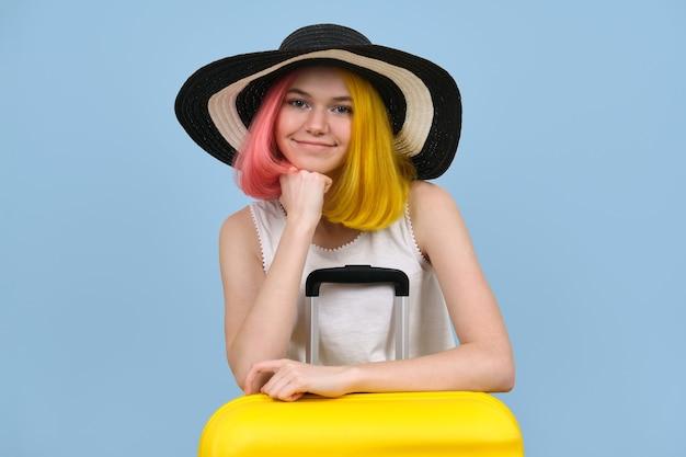 Retrato de estúdio de jovem com chapéu de verão com mala. menina adolescente feliz sobre fundo de cor azul. verão, férias, transporte, lazer, conceito de juventude