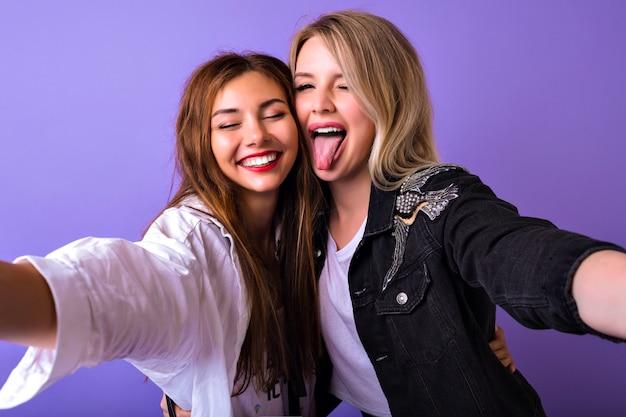 Retrato de estúdio de lindas irmãs melhores amigas, mulheres se divertindo juntas, sorrindo e gritando