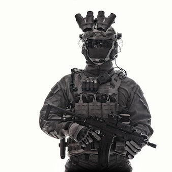 Retrato de estúdio de meio comprimento de lutador de esquadrão antiterrorista, soldado de operações especiais, mercenário da companhia militar com munição tática com dispositivo de visão noturna, rifle de assalto de cano curto armado