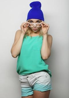 Retrato de estúdio de moda de uma bela jovem hippie loira com óculos, vestindo uma elegante camiseta urbana e um chapéu, sobre fundo branco