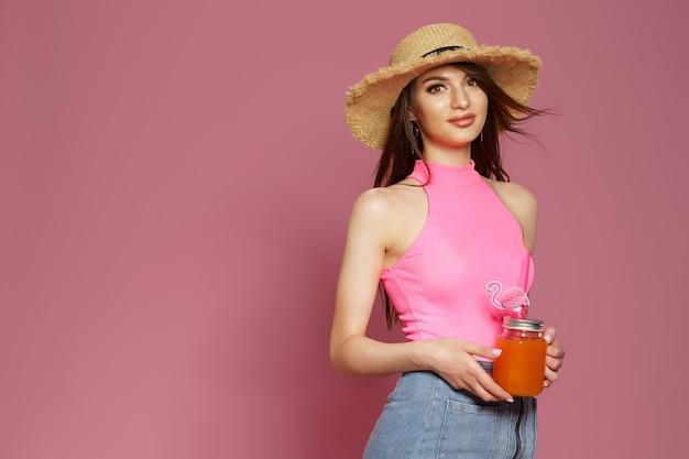 Retrato de estúdio de muito fofa adorável linda senhora segurando um copo de suco na mão usando canudo h.