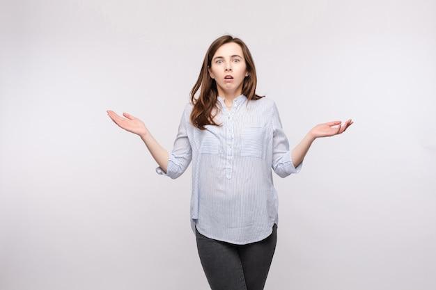 Retrato de estúdio de mulher morena em roupas casuais, mostrando perplexidade ou confusão e reagir com os braços para cima, com espanto - fotografia de stock # 132276038