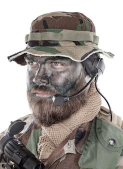 Retrato de estúdio de ombro de soldado de comando, mercenário moderno, soldado profissional com tinta de camuflagem preta no rosto barbudo, fone de ouvido tático de rádio com microfone, isolado no fundo branco