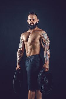 Retrato de estúdio de um homem barbudo tatuado sem camisa segurando halteres