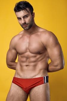 Retrato de estúdio de um homem musculoso e bronzeado, brutal, vestindo uma cueca vermelha em um amarelo
