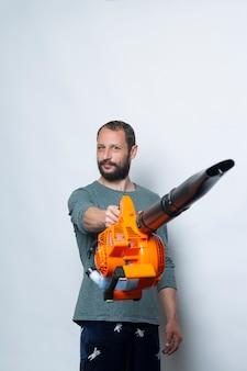 Retrato de estúdio de um homem segurando uma máquina sopradora com cara de raiva Foto Premium