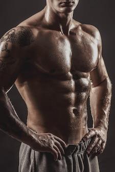 Retrato de estúdio de um homem tatuado e atlético sem camisa
