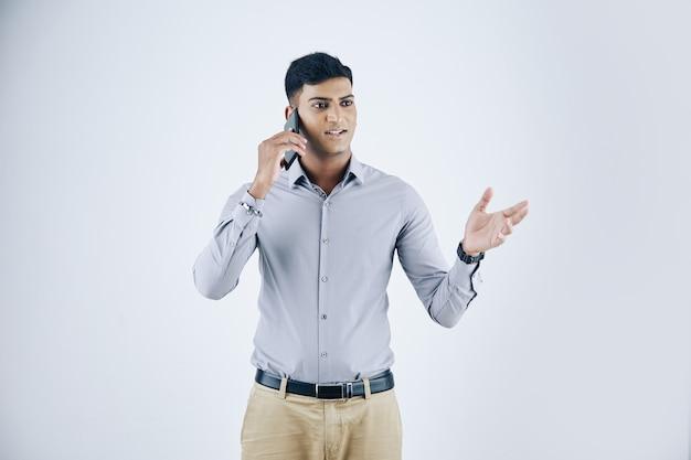 Retrato de estúdio de um jovem empresário indiano emocional gesticulando ativamente ao falar ao telefone