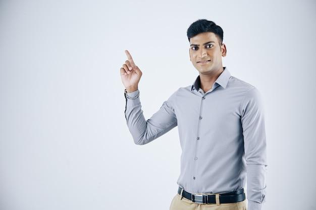 Retrato de estúdio de um jovem empresário indiano sorridente apontando com o dedo indicador