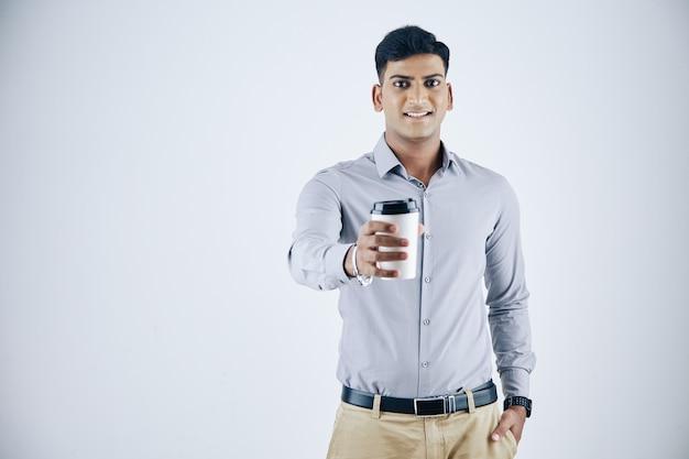 Retrato de estúdio de um jovem empresário indiano sorridente dando uma xícara de cappuccino para viagem