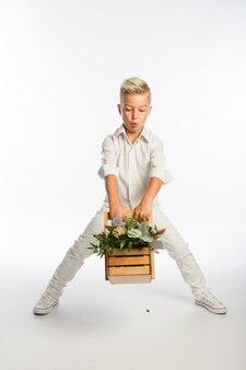 Retrato de estúdio de um menino caucasiano loiro na moda com uma cesta de flores de madeira, fundo branco, espaço de cópia