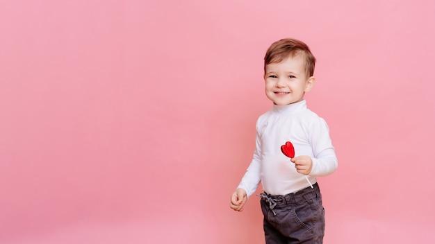 Retrato de estúdio de um menino feliz com um pirulito em forma de coração.