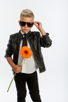 Retrato de estúdio de um menino loiro caucasiano elegante com uma única flor gerbera, fundo branco, espaço de cópia