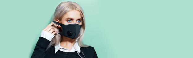 Retrato de estúdio de uma adolescente loira de olhos azuis, colocando máscara médica respiratória no rosto, proteção contra o coronavírus. fundo de banner panorâmico de aqua menta cor com espaço de cópia.