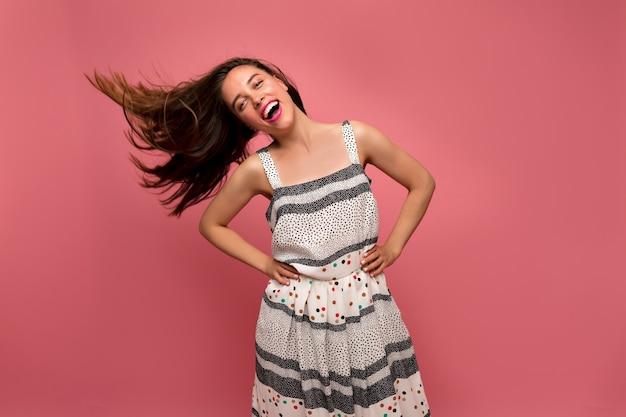 Retrato de estúdio de uma encantadora mulher atraente com cabelos castanhos ondulados, sorrindo e tocando seu cabelo, curtindo a vida sobre a parede rosa