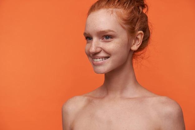 Retrato de estúdio de uma jovem atraente com cabeça de leitura com penteado coque isolado sobre fundo laranja, olhando para o lado com um sorriso encantador, demonstrando seus dentes brancos perfeitos