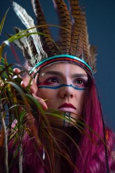 Retrato de estúdio de uma jovem com maquiagem e acessórios indígenas