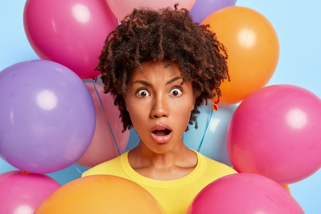 Retrato de estúdio de uma jovem espantada posando rodeada de balões coloridos de aniversário