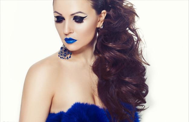 Retrato de estúdio de uma jovem morena linda com batom azul e brincos enormes com um casaco de pele azul