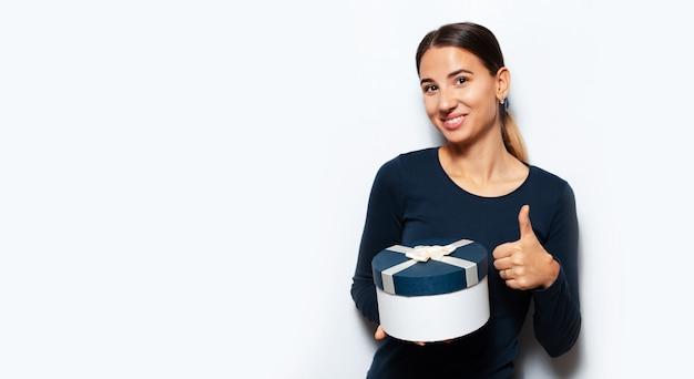 Retrato de estúdio de uma jovem segurando uma caixa de presente