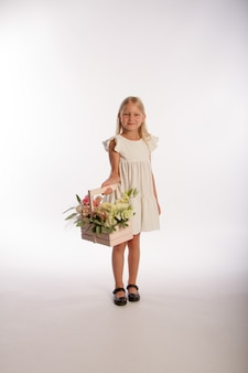 Retrato de estúdio de uma linda garota loira em um vestido branco com uma cesta de flores de madeira, fundo branco, foco seletivo