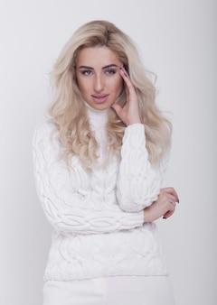 Retrato de estúdio de uma linda mulher loira cabelos compridos camisola quente no fundo branco
