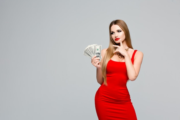 Retrato de estúdio de uma linda mulher vestida de vermelho detém o dinheiro e pensa onde gastá-lo. jovem esbelta com maquiagem brilhante, lábios vermelhos, cabelo loiro comprido e reto, notas de 100 dólares nas mãos.