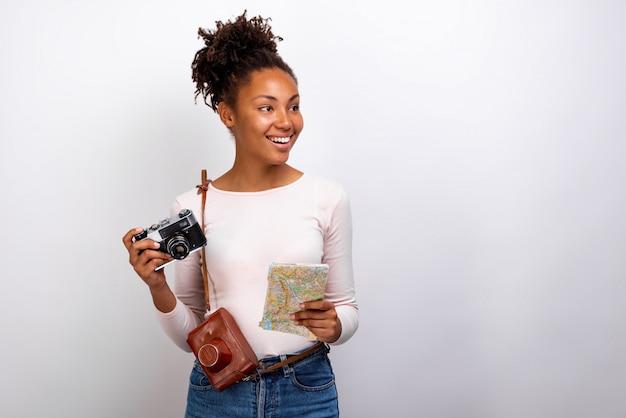 Retrato de estúdio de uma menina feliz viajante mulata com câmera fotográfica e um mapa em suas mãos e olhando de soslaio