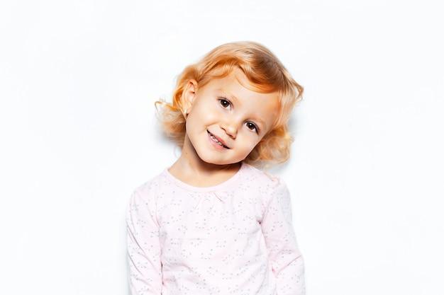 Retrato de estúdio de uma menina sorridente com cabelo loiro encaracolado