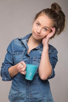 Retrato de estúdio de uma mulher com sono em uma camiseta laranja com uma xícara de café na mão