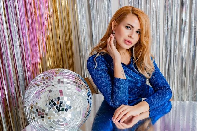 Retrato de estúdio de uma mulher loira elegante com maquiagem perfeita e bola de discoteca