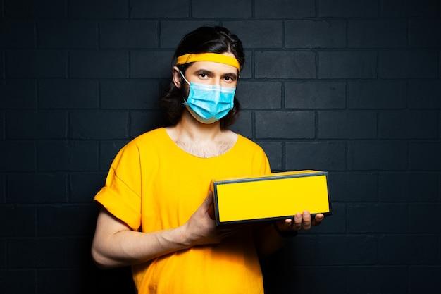 Retrato de estúdio do jovem entregador segurando uma caixa amarela, vestindo máscara médica e camisa laranja no fundo da parede de tijolo preto.