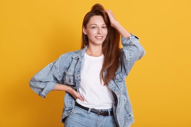Retrato de estúdio do modelo de uma linda mulher com cabelos longos escuros bonitos, vestindo jaqueta jeans e camisa branca, posando isolado sobre amarelo