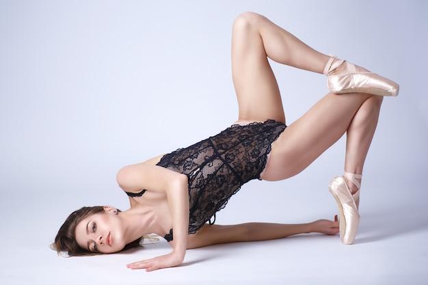 Retrato de estúdio em comprimento total de uma linda garota com uma figura esportiva em um body de renda na ponta