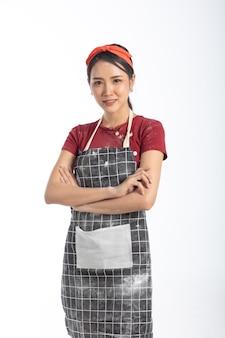 Retrato de estúdio jovem atraente usando avental fazendo padaria em fundo branco