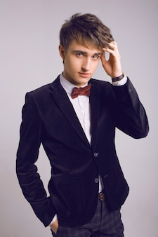 Retrato de estúdio moda de homens bonitos em terno de luxo elegante e gravata borboleta, fundo claro, cores suaves.