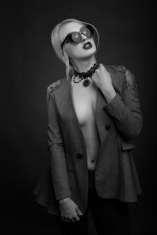 Retrato de estúdio preto e branco de uma mulher loira sexy usando óculos escuros e jaqueta em um corpo nu